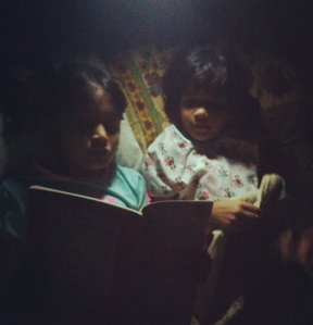 Aanya can often be found sharing a torch to read with her little sister Diya.